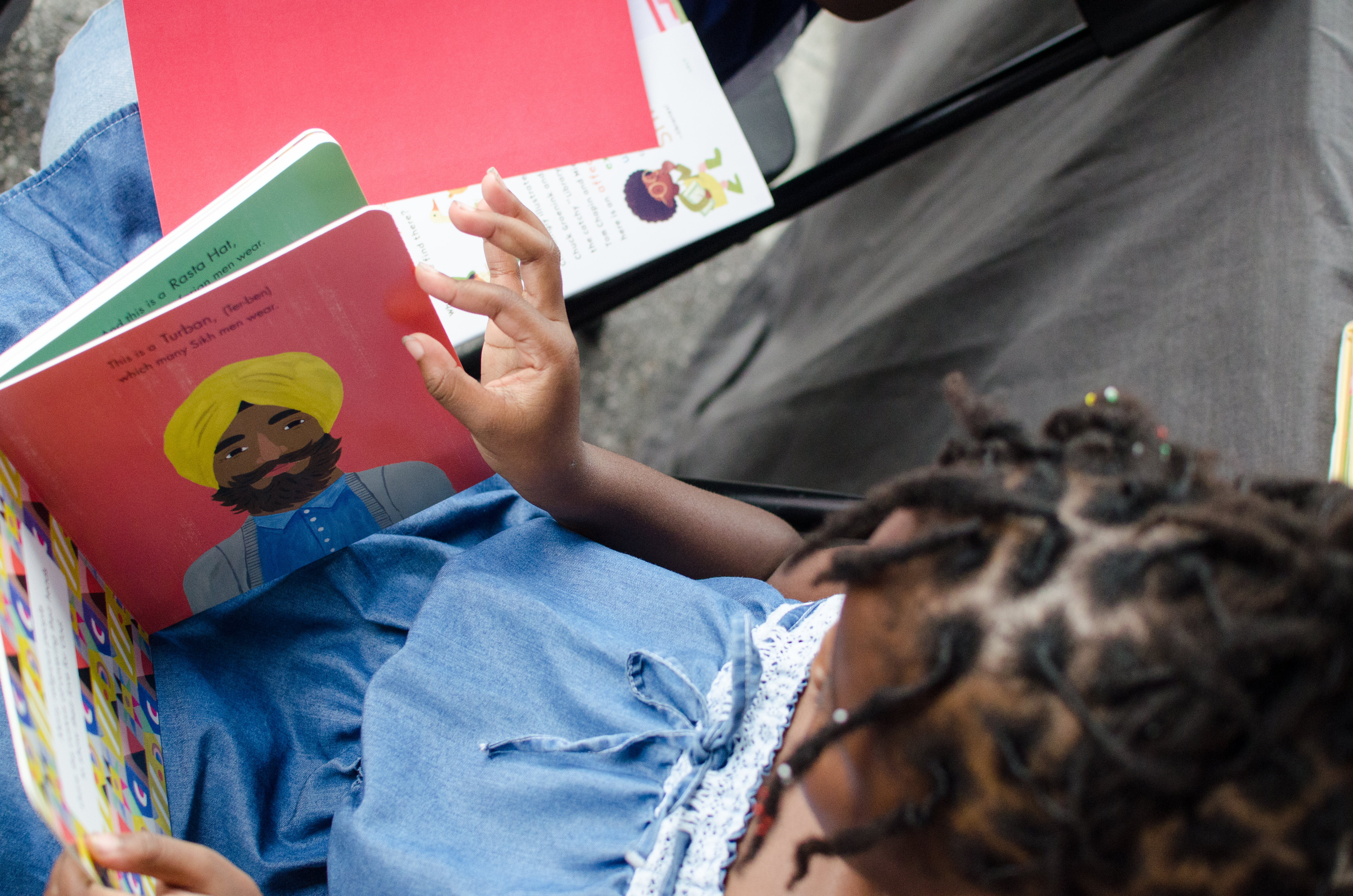 Black child reading board book with pictures depicting head dressings.