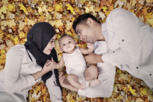 Image of cute male baby lying on the autumn leaves with his parents