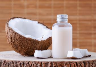 cosmetic bottle and fresh organic coconut for skincare, natural brown background
